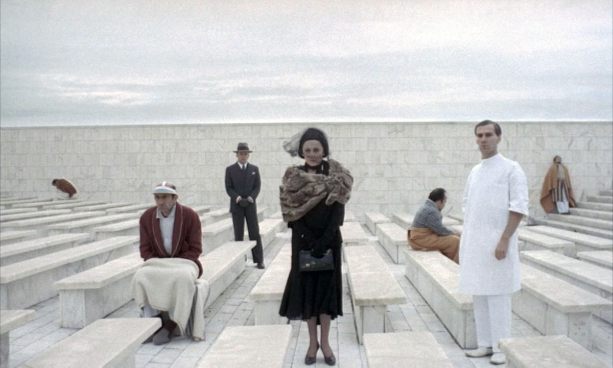 With his mother (Carla Mignone, center), Fascist state operative Marcello Clerici (Jean-Louis Trintignant; standing, in suit and hat) visits his father at an insane asylum. These scenes were filmed at the Piazza John Fitzgerald Kennedy, in the Palazzo dei Ricevimenti e dei Congressi dell'EUR, in Rome, Italy.