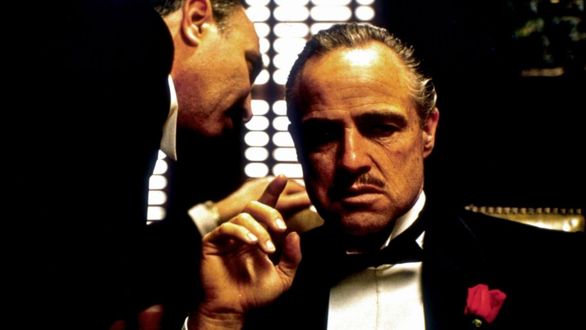 "On the day of his daughter's wedding, mob boss Don Vito Corleone (Marlon Brando) listens to a private request for revenge made by a distraught undertaker, Bonasera (Salvatore Corsitto), whose daughter has been beaten and disfigured by a group of thugs. Although director Francis Ford Coppola and cinematographer Gordon Willis, ASC had established a ""no zooms"" rule for the movie, they suspended this policy for Bonasera's initial monologue, when the camera introduces the character in a tight close-up before zooming back slowly to reveal the Don's dark, somber den and the side of his face. ""The zoom-out seemed to take forever while the actor was talking, but it worked,"" Willis recalled. ""It was applied in a very particular fashion for that one scene, and we never used a zoom again on the Godfather pictures. The scene serves to introduce our main character in an interesting way. We hold back, hold back, hold back and then bop — we cut around to a big, frontal close-up of Brando, which is a wonderful way to introduce Don Corleone."""
