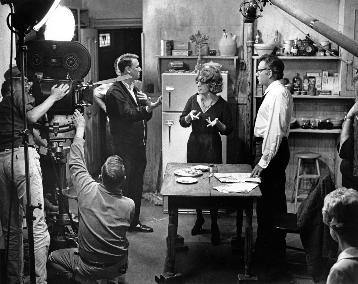 Director Mike Nichols confers with his stars. The kitchen was lit realistically to look flat and drab. Single cone light mounted overhead was used as key with very little fill from the floor and no attempt to gobo light with flags and cutters. Flat lighting in this sequence also provided visual variety, because the bulk of film is photographed with light of harsh contrast.
